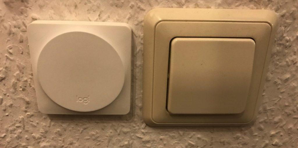 Foto von einem Logitech-Pop-Schalter neben einem klassischem Lichtschalter